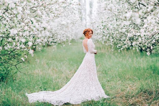 Uma jovem mulher com um vestido de noiva está em um jardim florido de primavera