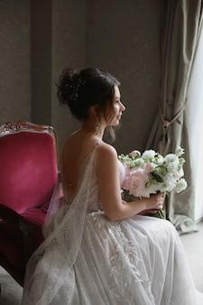 Uma jovem mulher com um vestido de noiva vintage com um buquê de flores está sentada em uma cadeira antiga no interior
