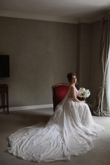Uma jovem mulher com um vestido de noiva vintage com um buquê de flores está sentada na cadeira no interior vintage