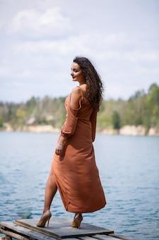 Uma jovem mulher com um vestido fica em alvenaria de madeira no meio de um lago azul. menina feliz sorri e o sol brilha, dia de verão. ela tem cabelos longos e cacheados e uma aparência europeia