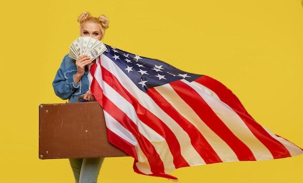 Uma jovem mulher com uma bandeira americana tem nas mãos uma mala de viagem e notas de dinheiro. rosto alegre surpreso.