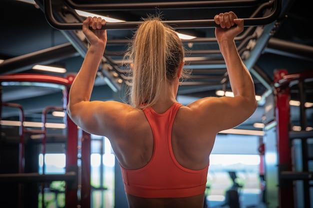 Uma jovem mulher com uma figura de esportes praticando no ginásio, fitness e musculação