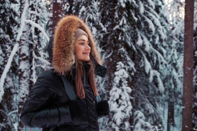 Uma jovem mulher com uma jaqueta de inverno com capuz de pele caminha na floresta no inverno. bela natureza gelada, floresta de pinheiros na neve.
