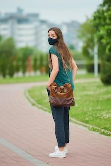 Uma jovem mulher com uma máscara médica azul marinho caminha no parque