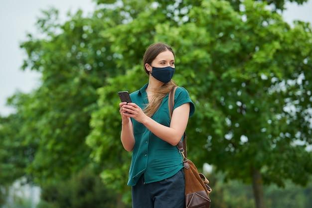 Uma jovem mulher com uma máscara médica azul marinho, segurando um smartphone com as duas mãos enquanto caminhava no parque