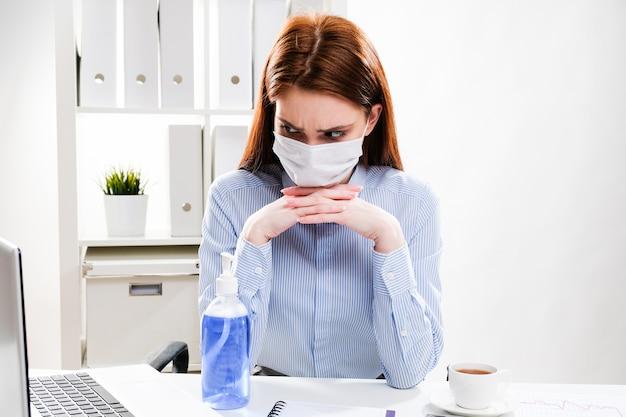 Uma jovem mulher com uma máscara protetora olha pensativa para um computador. mulher de negócios em uma máscara médica no escritório.