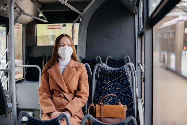 Uma jovem mulher com uma máscara usa transporte público sozinha, durante uma pandemia.