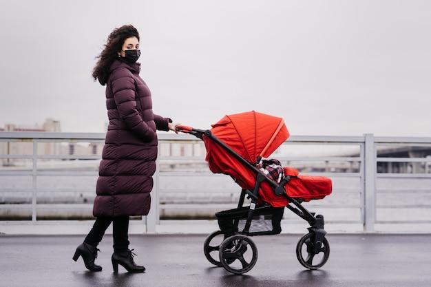 Uma jovem mulher com uma máscara, vestida com uma jaqueta quente na rua da cidade, rola um carrinho de bebê na frente dela
