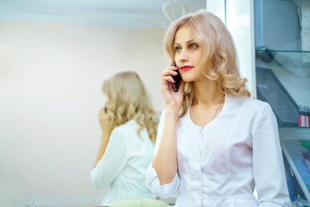 Uma jovem mulher com uma túnica branca chamando no telefone no escritório de uma esteticista.