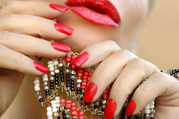 Uma jovem mulher com unhas e lábios cor de coral com um acessório na mão.