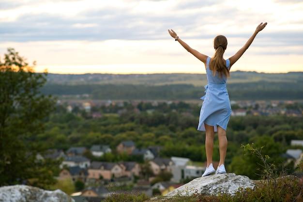 Uma jovem mulher com vestido de verão, levantando as mãos em pé ao ar livre, apreciando a vista do pôr do sol amarelo brilhante.