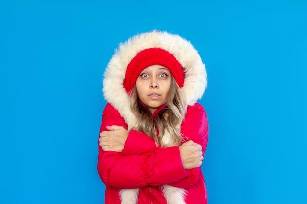 Uma jovem mulher congelada em uma jaqueta vermelha quente e chapéu treme abraçando a si mesma