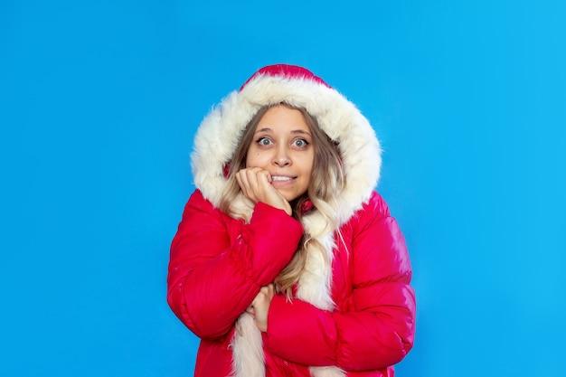 Uma jovem mulher congelada em uma jaqueta vermelha quente estremece abraçando-se no fundo de cor azul