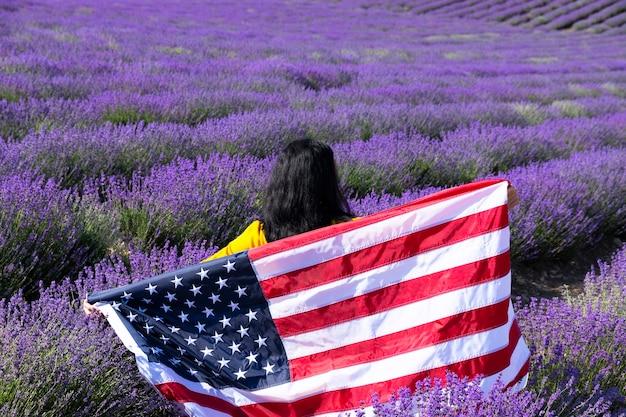 Uma jovem mulher de cabelos escuros segurando a bandeira dos estados unidos da américa contra o céu ensolarado. dia do memorial e conceito do dia da independência dos eua.