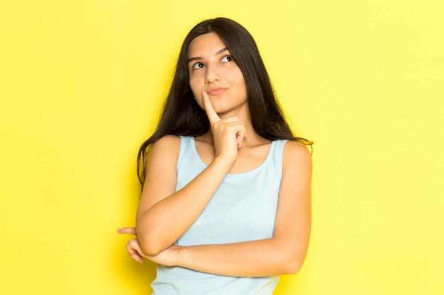 Uma jovem mulher de camisa azul, vista frontal, posando com expressão pensativa
