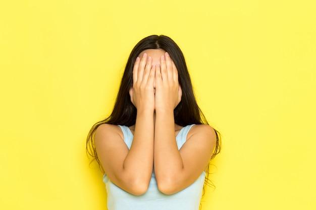 Uma jovem mulher de camisa azul, vista frontal, posando e cobrindo o rosto com as mãos