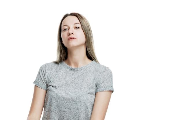 Uma jovem mulher de camiseta cinza está olhando arrogantemente para a câmera. egoísmo. isolado em uma parede branca