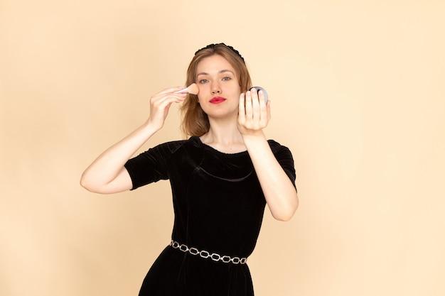 Uma jovem mulher de frente para o vestido preto com cinto de corrente fazendo maquiagem em bege