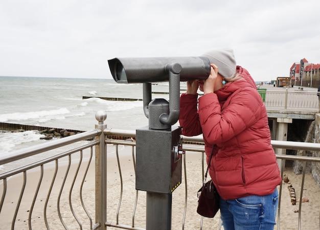 Uma jovem mulher de jaqueta e calça jeans olha através de um telescópio público à beira-mar e observa um belo panorama do mar báltico