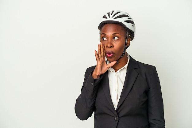 Uma jovem mulher de negócios afro-americana usando um capacete de bicicleta isolado no fundo branco está contando uma notícia secreta de travagem e olhando para o lado