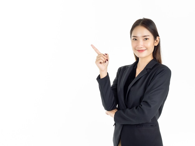 Uma jovem mulher de negócios asiática atraente em terno preto apontando o dedo para apresentar no espaço da cópia e olhando a câmera.