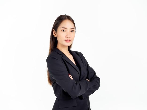 Uma jovem mulher de negócios asiática confiante em um terno preto, com os braços cruzados