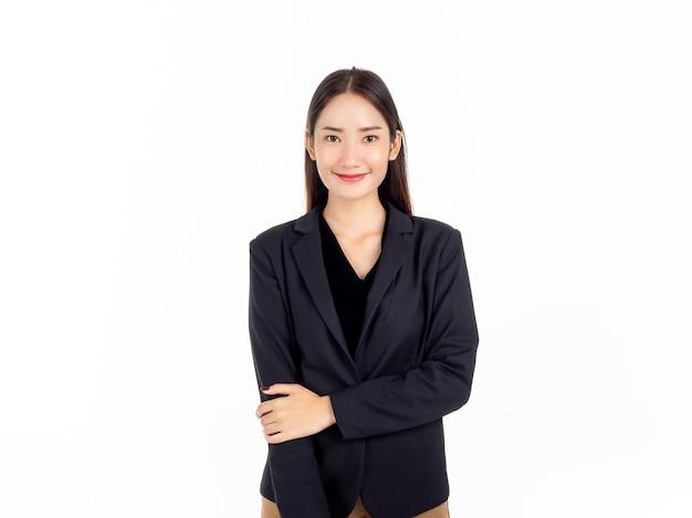 Uma jovem mulher de negócios asiática confiante em um terno preto com um sorriso, e está de pé com os braços enrolados de forma humilde