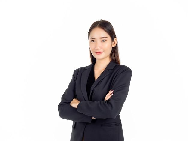 Uma jovem mulher de negócios asiática confiante em um terno preto com um sorriso e os braços cruzados