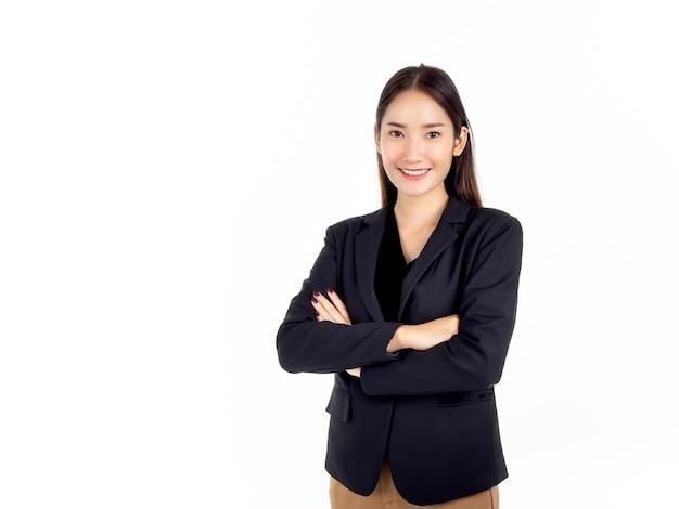 Uma jovem mulher de negócios asiática confiante em um terno preto sorrindo, de pé com os braços cruzados e olhando para a câmera isolada no branco