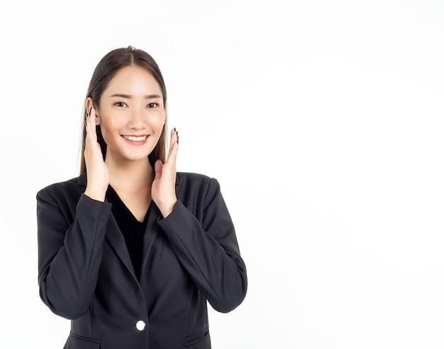 Uma jovem mulher de negócios asiática em um terno preto segurando as mãos nas bochechas com um sorriso feliz e olhando para a câmera
