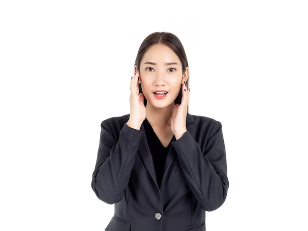 Uma jovem mulher de negócios asiática em um terno preto segurando as mãos no rosto com um sorriso animado e olhando para a câmera