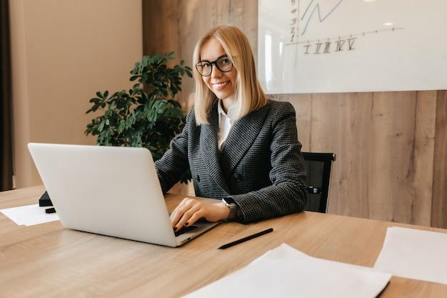 Uma jovem mulher de negócios de sucesso está sentada em um local de trabalho em seu escritório como diretora de empresa. trabalhador do centro de negócios.