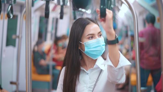Uma jovem mulher de negócios está usando máscara no transporte público, viagens seguras, conceito de proteção covid-19.