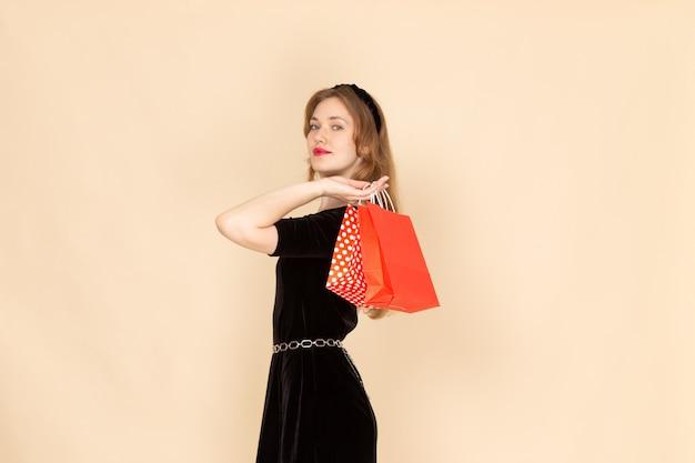 Uma jovem mulher de vestido preto com correntes segurando pacotes em bege