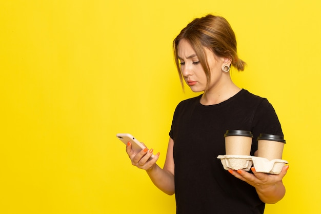 Uma jovem mulher de vestido preto, vista frontal, segurando xícaras de café e usando um telefone amarelo