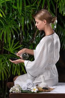 Uma jovem mulher derrama óleo de massagem em uma tigela. preparação para tratamentos de spa