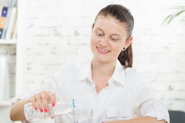 Uma jovem mulher derrama um copo de água