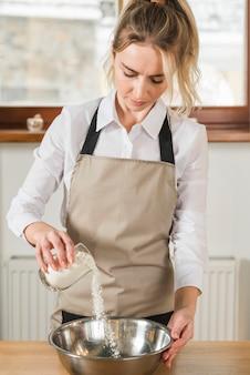 Uma jovem mulher derramando a farinha do copo na tigela de aço inoxidável de mistura