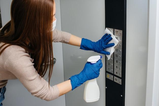 Uma jovem mulher desinfecta e limpa as chaves no elevador durante uma pandemia global. ficar em casa