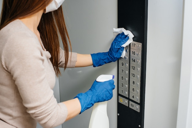 Uma jovem mulher desinfeta e limpa as chaves em um elevador durante uma pandemia global. ficar em casa.