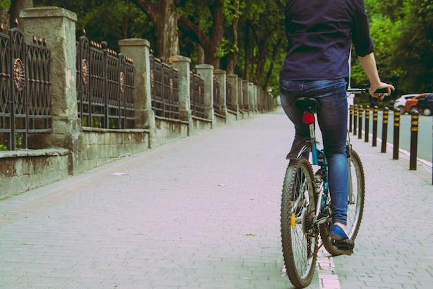 Uma jovem mulher é andar de bicicleta no pôr do sol no parque vintage