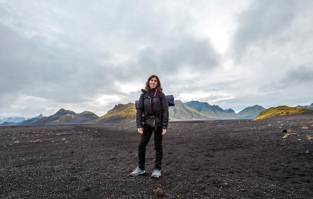 Uma jovem mulher em cinzas vulcânicas e uma montanha verde. landmannalaugar, islândia