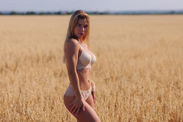 Uma jovem mulher em roupas íntimas em um campo de trigo.