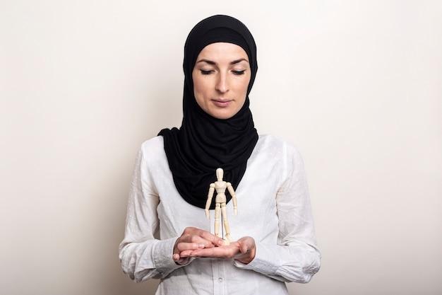 Uma jovem mulher em um hijab está segurando olha para um fantoche de um homem de madeira sobre um fundo claro.