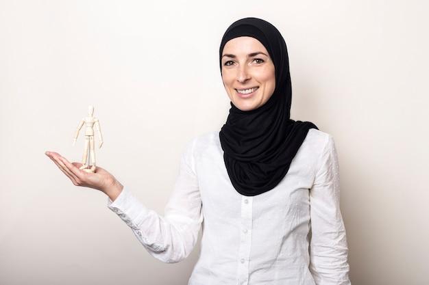 Uma jovem mulher em um hijab na palma da mão segura um homem de madeira sobre um fundo claro.