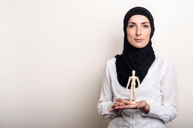 Uma jovem mulher em um hijab segura uma marionete de um homem de madeira sobre um fundo claro.