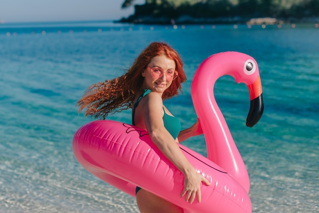 Uma jovem mulher em um maiô com cabelos ruivos balançando ao vento está de pé na praia em um dia ensolarado.