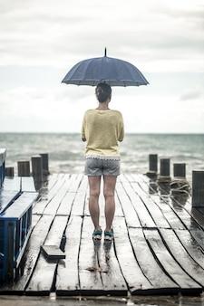 Uma jovem mulher em um píer com um guarda-chuva