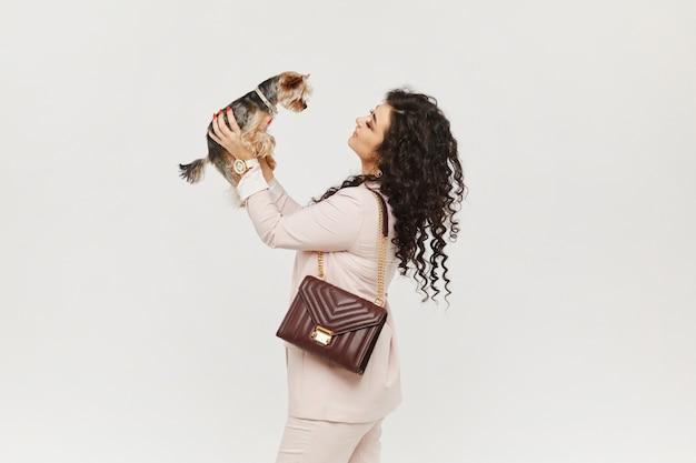 Uma jovem mulher em um terno bege segurando yorkie terrier nas mãos