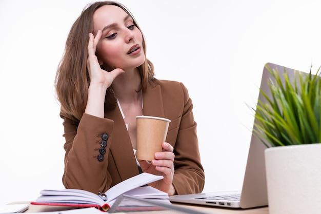 Uma jovem mulher em um terno marrom bebe café no local de trabalho. isolado